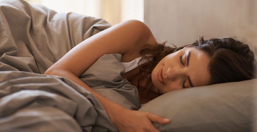 Mulher dormindo de lado em cima da cama