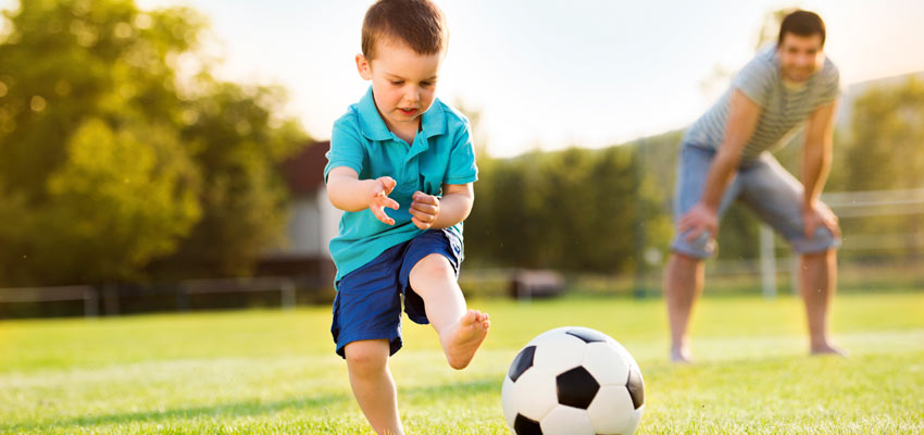 Criança jogando bola com o pai ao fundo