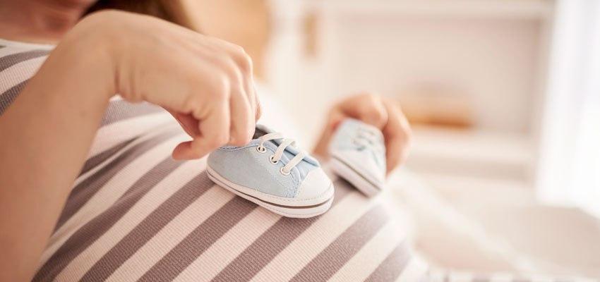 Mulher grávida com dois sapatinhos azuis em cima da barriga