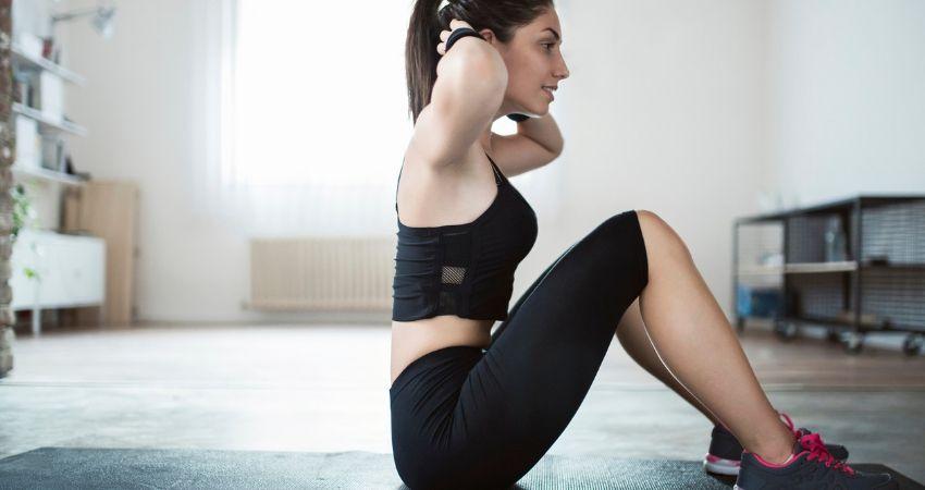 Mulher na sala de casa fazendo abdominais