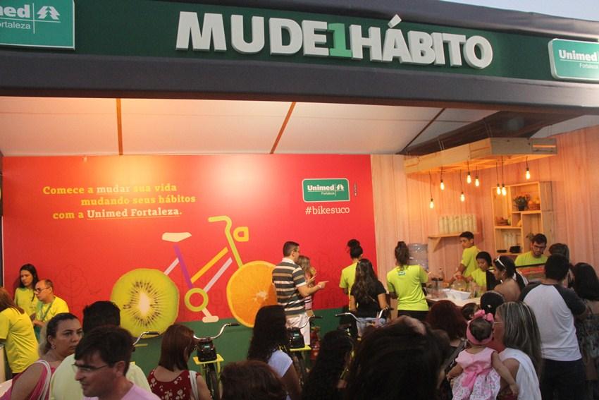 Stand da Unimed Fortaleza com muitas pessoas aguardando para fazer seu suco na bicicleta