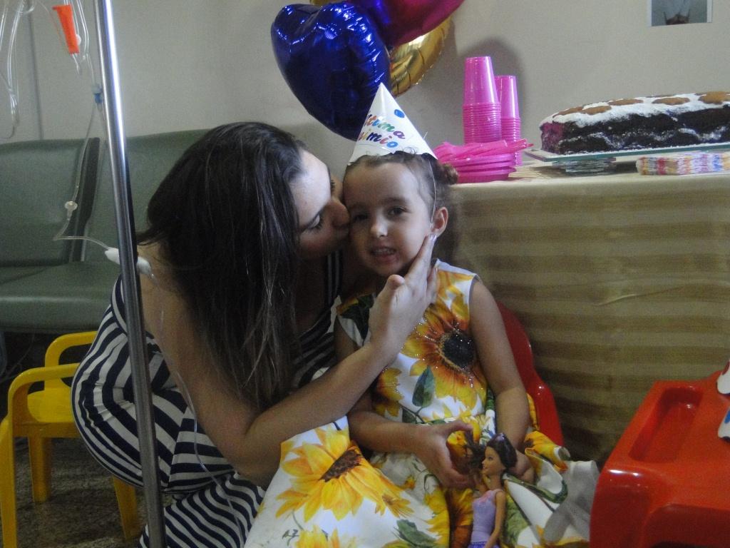 Giovanna vestida com vestido floral e um chapéuzinho de aniversário sendo beijada no resto pela sua mãe