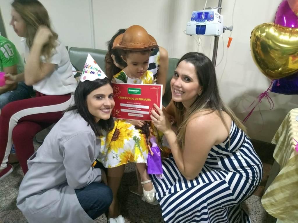 Uma enfermeira e a mãe de Giovanna segurando o certificado de fim do tratamento com Giovanna ao fundo.