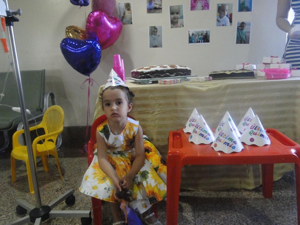 Giovanna vestida com vestido floral e um chapéuzinho de aniversário em sua festa de despedida do hospital