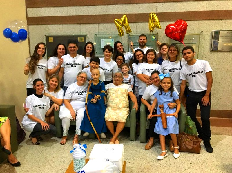 Familiares da Maria Alice junto com ela, sorridentes e felizes na recepção do Hospital Regional Unimed