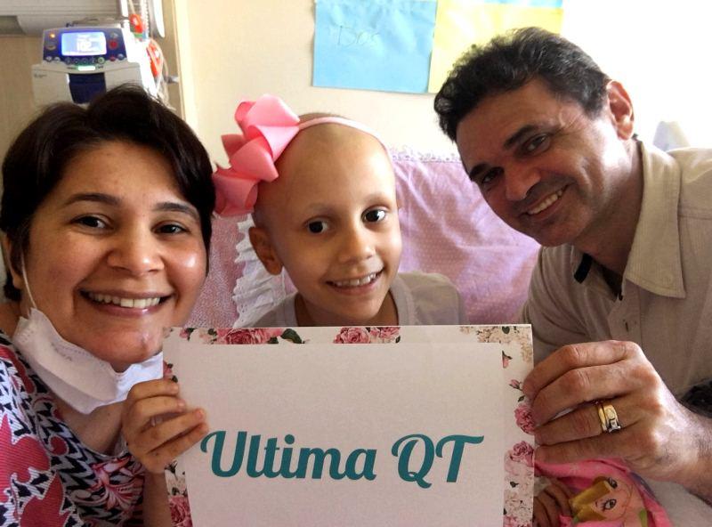 """Maria Alice sorridente segurando um cartaz com o texto """"Ultima QT"""" ao lado de seus pais"""