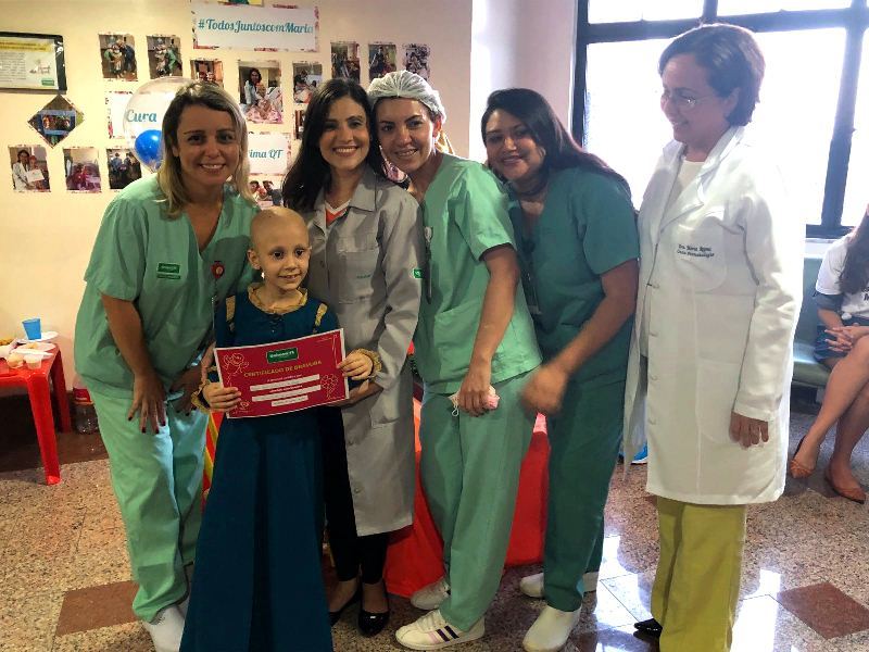 Maria Alice segurando certificado junto com enfermeiras e médica