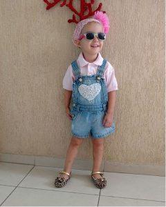 Giovanna de óculos, vestida com um macacão e blusa rosa, ainda careca durante o tratamento, com uma faixa e pompom rosa na cabeça.
