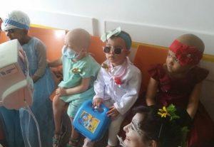 Giovanna durante o tratamento, sem cabelo e totalmente caracterizada de médica, com outras crianças caracterizadas, todas sentadas nos bancos do hospital