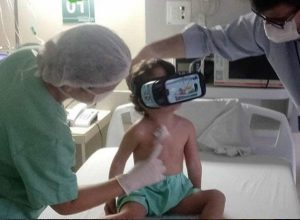 Giovanna sentada na cama do hospital, experimentando o óculos de Realidade Virtual oferecido pela Unimed Fortaleza
