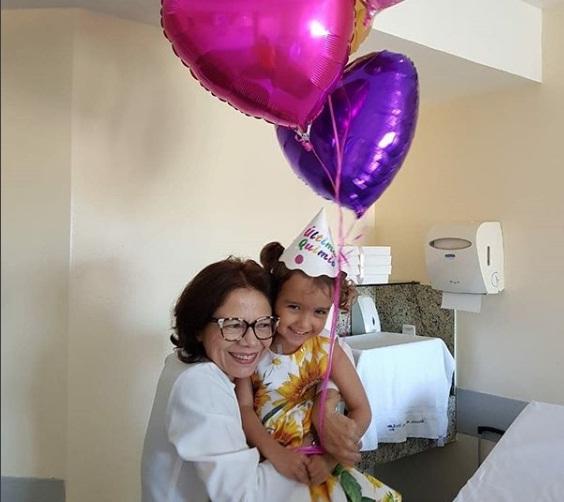 Giovanna vestida com vestido floral e um chapéuzinho de aniversário, segurando balões de coração, sendo abraçada pela sua médica