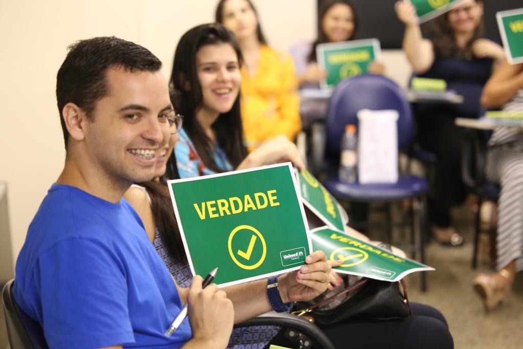 """Um dos participantes segurando uma placa verde escrito """"verdade"""""""