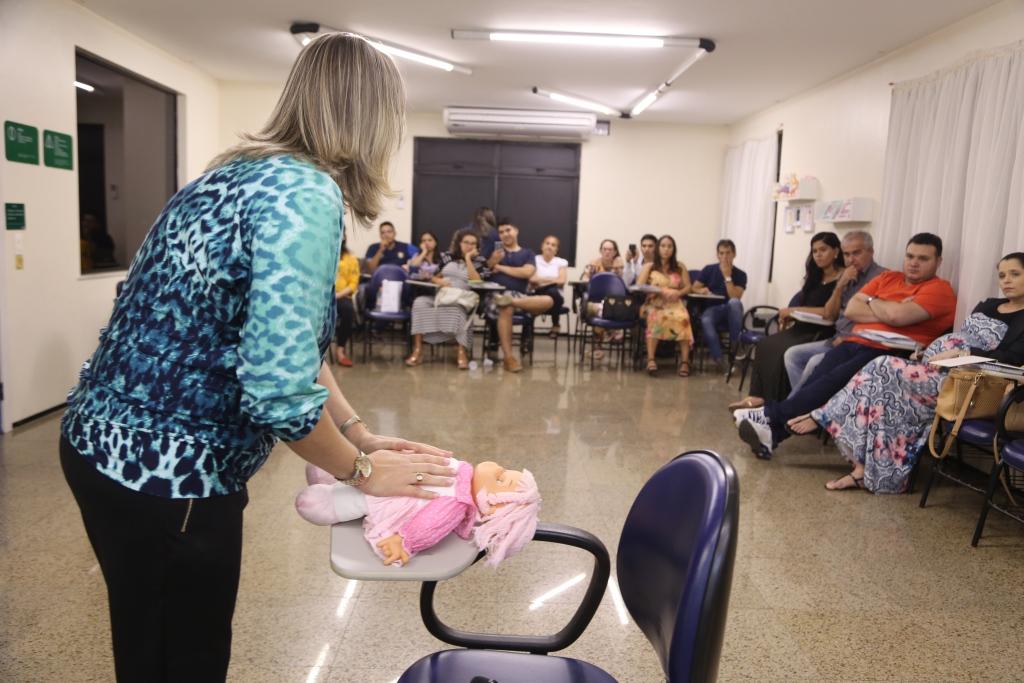 Uma das palestrantes mostrando movimentos com uma boneca que devem ser feitos no bebê