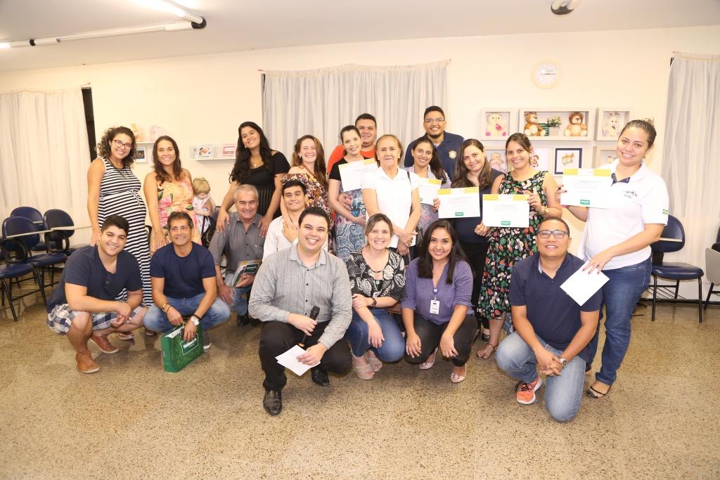 Participantes do Dia de Mama segurando certificados de participação e sorrindo para a foto juntos