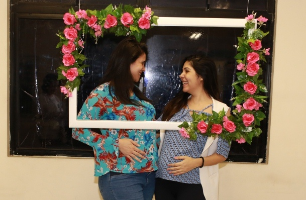 Mulheres grávidas se olhando sorrindo atrás de um painel florido