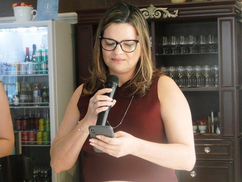 Mais uma participantes do Roda de Vida com microfone na mão e lendo algo na tela do celular