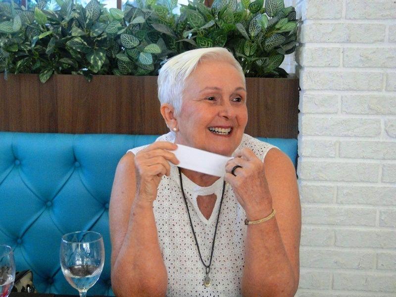 Uma das participantes do roda de vida com um papelzinho na mão e sorrindo