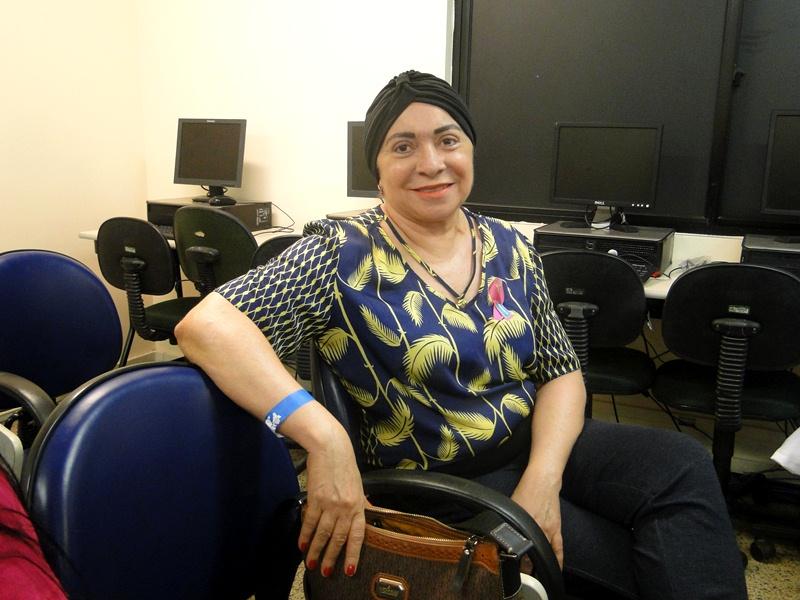 Uma das participantes da palestra e paciente da oncologia do HRU com turbante na cabeça sorrindo para a camera