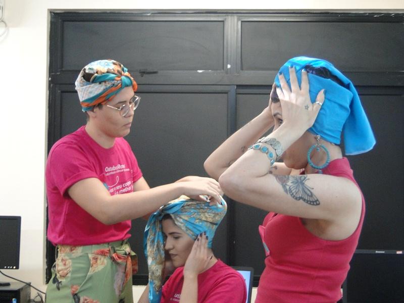 Participantes da palestra aprendendo a usar lenço na cabeça