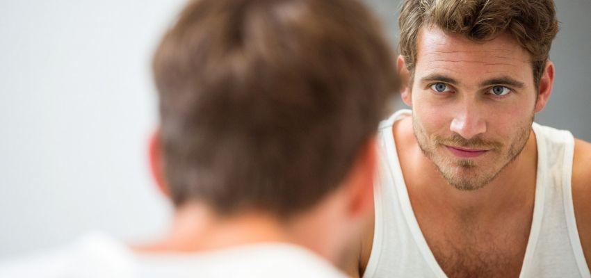 Homem analisando seu rosto em frente ao espelho