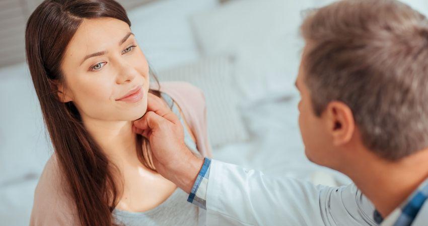 Médico Endocrinologista examinando pescoço de paciente