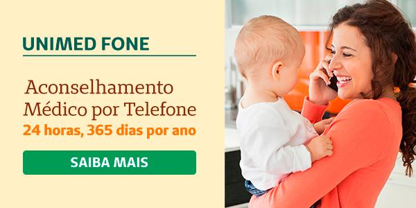 mãe com filho no colo em casa falando ao telefone