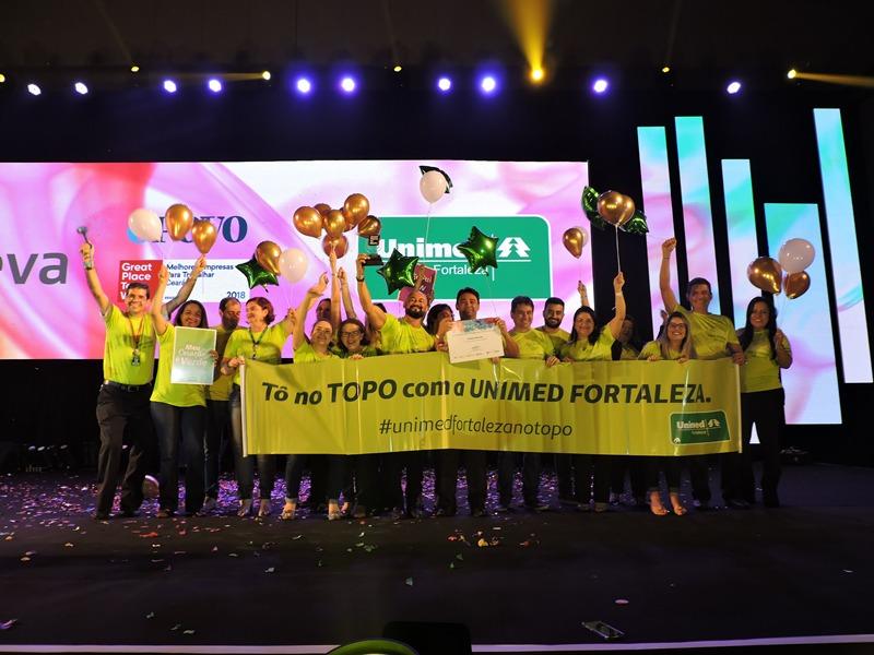 Colaboradores da Unimed Fortaleza no palco comemorando o título de 5ª melhor empresa para se trabalhar no Ceará
