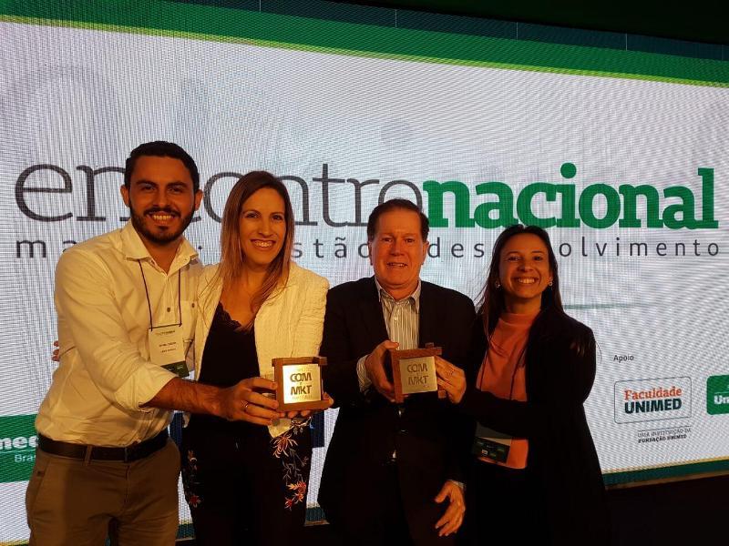 Colaboradores da Unimed Fortaleza ao lado do Diretor Comercial, Dr. João Borges, segurando os prêmios recebidos pela Unimed Brasil.