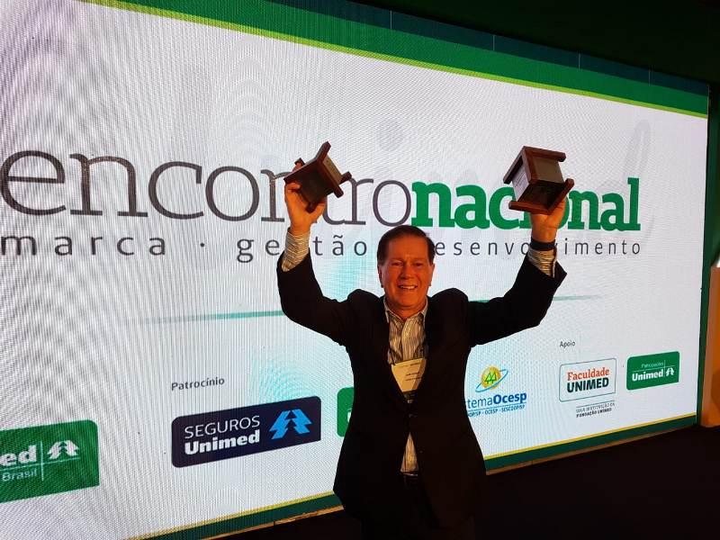 Diretor comercial, Dr. João Borges, segurando os dois prêmios recebidos pela Unimed Brasil.