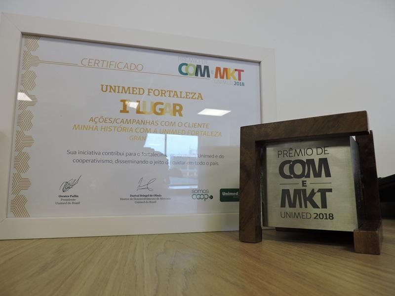 Certificado de homenagem ao lado do prêmio de 1º lugar na categoria Ações/Campanhas com o cliente