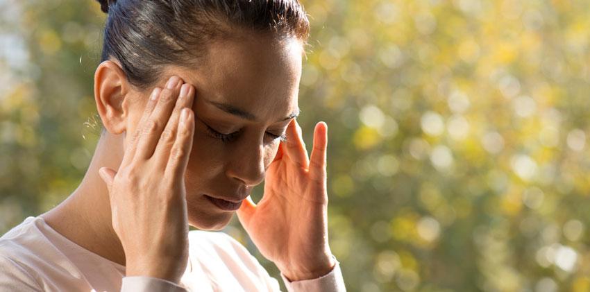 Mulher preocupada com as mãos na cabeça provavelmente com um cansaço mental