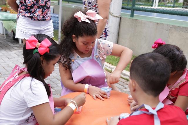 Crianças brincando em uma mesa no evento Dia da Familia