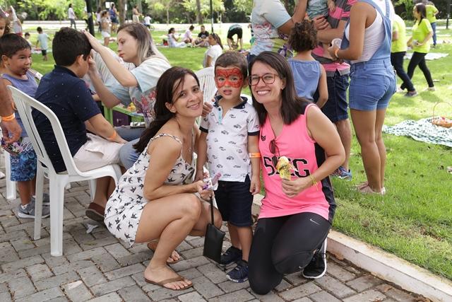 Colaboradores da Unimed Fortaleza com seus filhos sorrindo para a foto no evento Dia da Familia