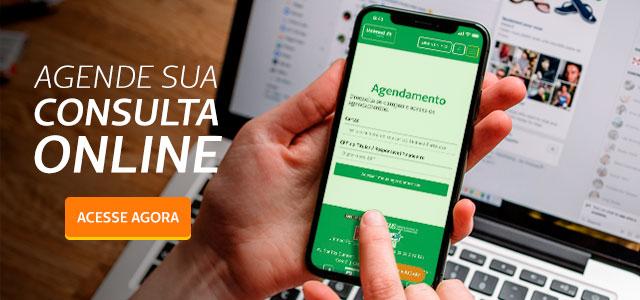 Mão segurando um celular na tela de agendamento online da Unimed Fortaleza