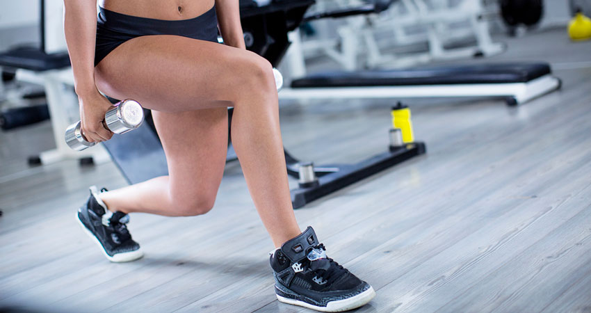 Mulher realizando agachamento com peso mostrando que exercícios evitam sinais de trombose na perna