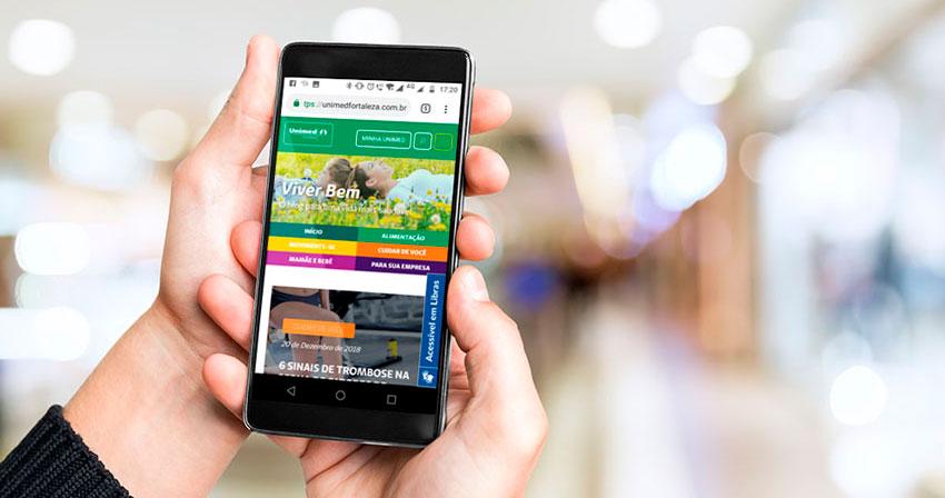 Mão segurando smartphone na tela do Blog Viver Bem vendo posts publicados em 2018 mais acessados no ano.