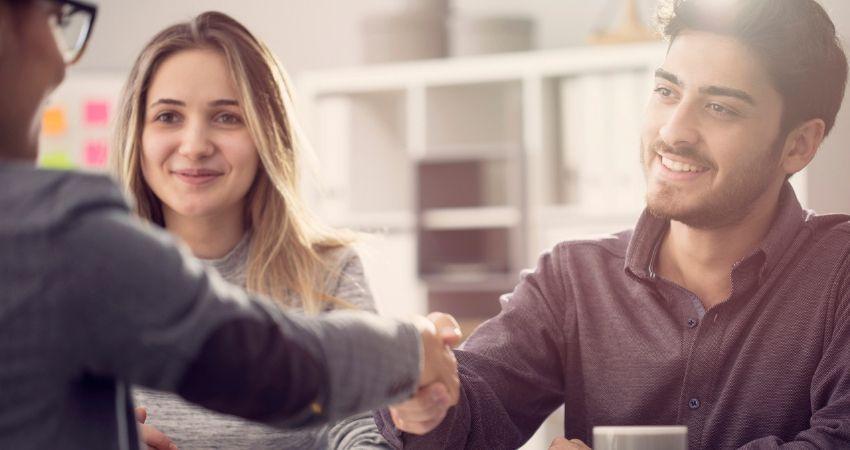 Funcionário sorridente cumprimenta sua gestora com um aperto de mão e celebra o novo plano de cargos e salários da empresa
