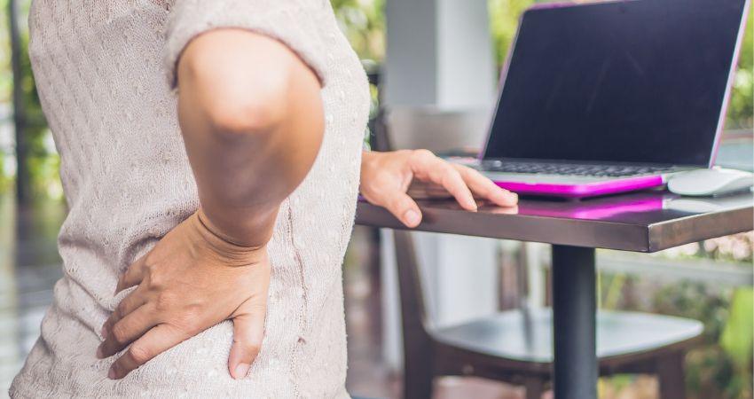 Mulher com a mão na lombar sentindo as dores causadas pela hérnia de disco