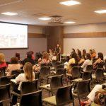 Participantes assistindo palestra no evento especial do Dia da Mulher