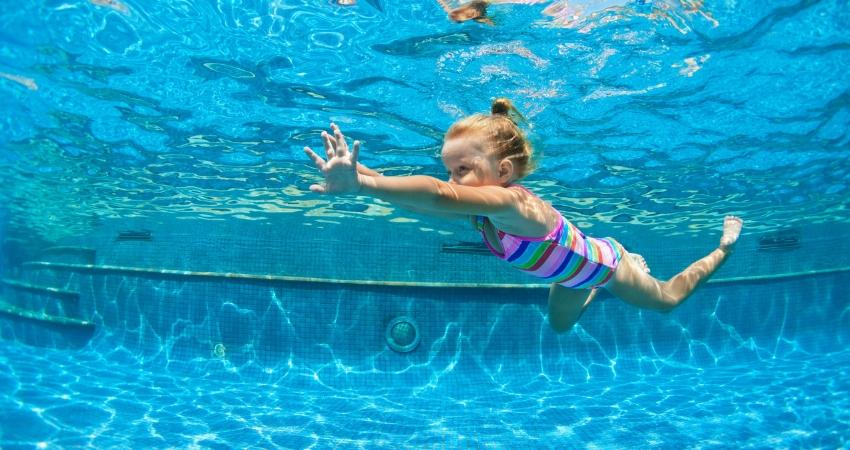 Garotinha nadando em uma grande piscina