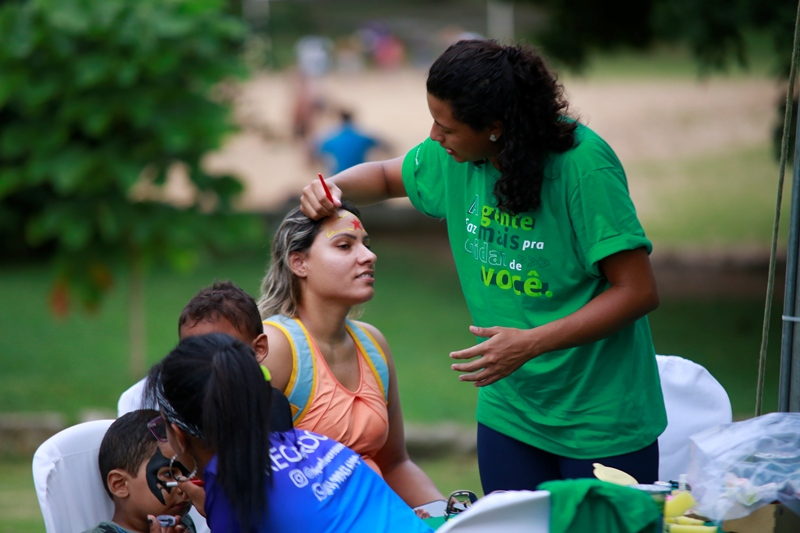 Mulheres pintando o rosto de crianças e adultos durante o evento