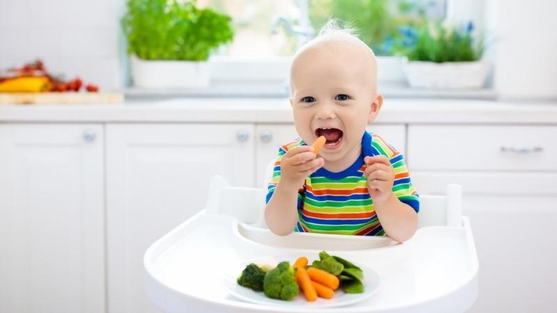 Bebê sentado em uma cadeirinha enquanto leva os alimentos até a boca como no método blw