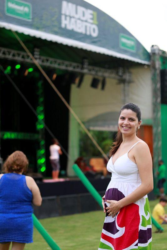 Foto de uma mulher grávida com o palco do evento ao fundo