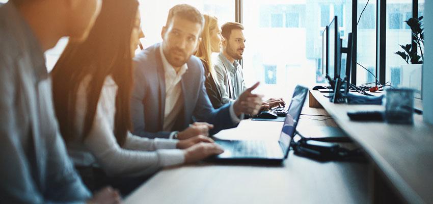 Equipe de RH trabalhando em uma mesa com vários computadores, além do Business Partner