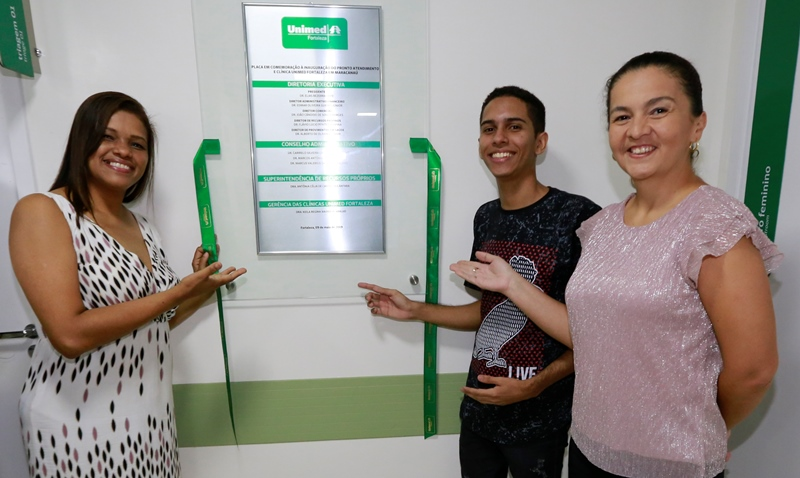 Alguns colaboradores da nova unidade com a placa de inauguração