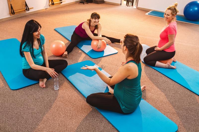 Grávidas juntas realizando exercícios em colchonetes