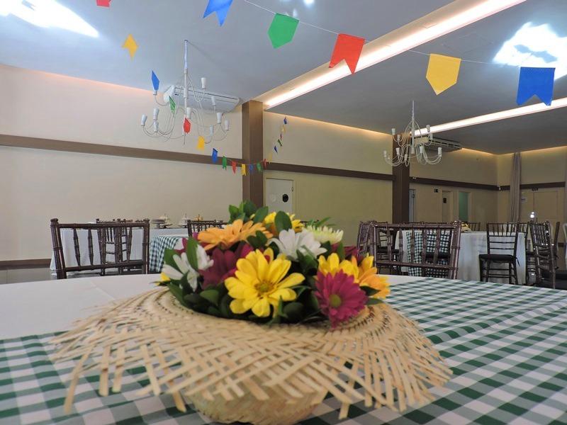 Chapéu de palha com flores em cima de uma mesa no São João do Roda de Vida