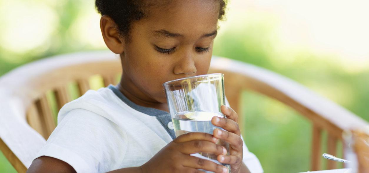 Criança bebendo água para ilustrar texto que fala dos sinais de desidratação
