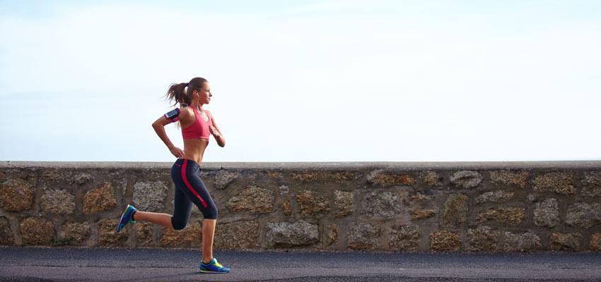 Mulher correndo em jejum com muro ao fundo
