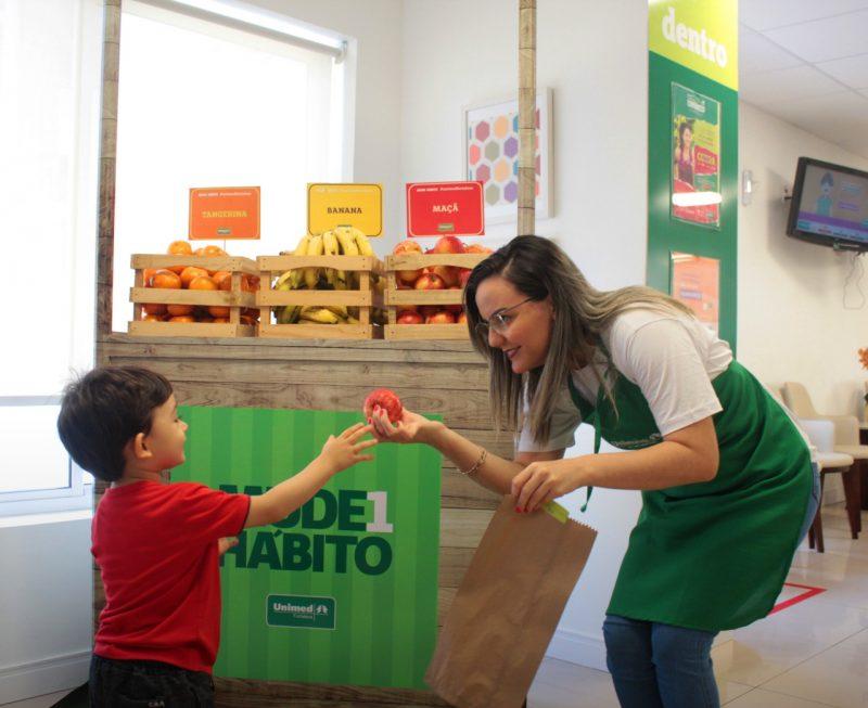 Criança recebendo fruta de uma mulher